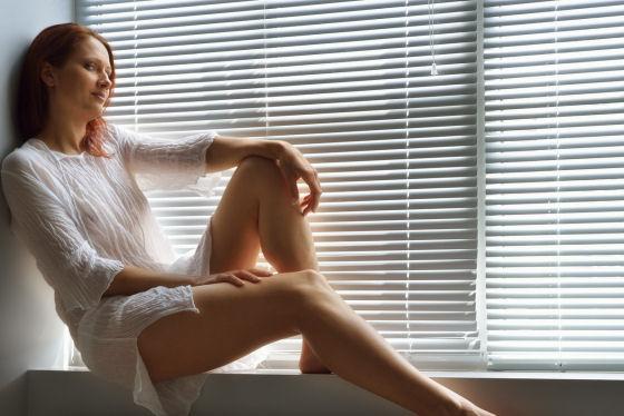 Frau an Fenster mit Jalousie