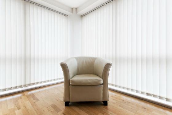 Fenster-Eck mit beigem Sessel und weißen Vertikaljalousien